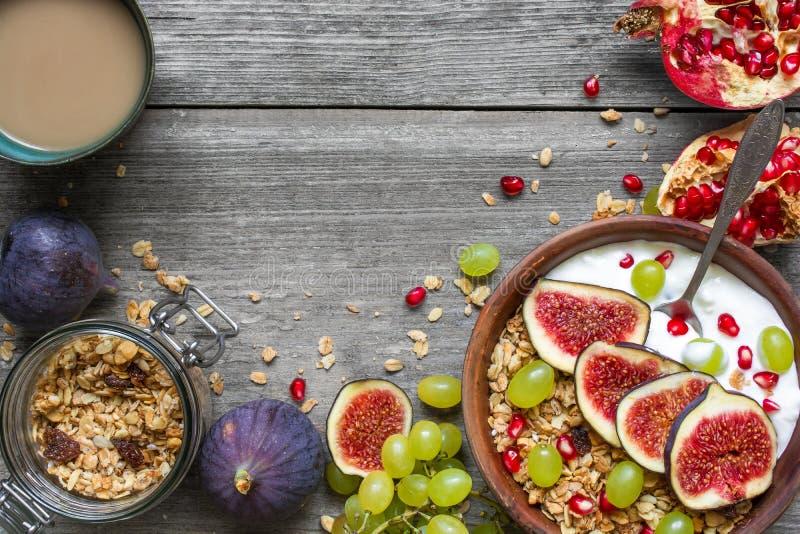 Υγιές κύπελλο προγευμάτων του granola βρωμών με το γιαούρτι, τους σπόρους ροδιών, τα σύκα, το σταφύλι και τα καρύδια με ένα κουτά στοκ εικόνα με δικαίωμα ελεύθερης χρήσης