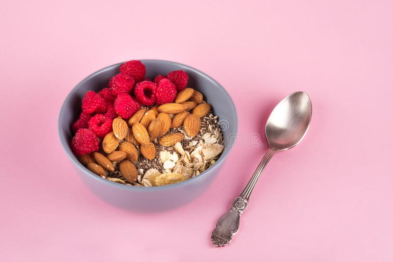 Υγιές κύπελλο προγευμάτων: oatmeal με το σμέουρο, το αμύγδαλο, και τους σπόρους chia Αγροτικό κουτάλι Ρόδινο υπόβαθρο κρητιδογραφ στοκ εικόνες