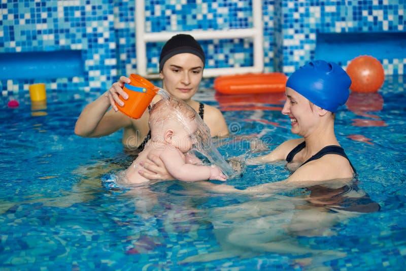 Υγιές μωρό διδασκαλίας οικογενειακών μητέρων που κολυμπά με τη βοήθεια εκπαιδευτικών στη λίμνη Λεωφορείο που πραγματοποιεί τη σει στοκ φωτογραφία με δικαίωμα ελεύθερης χρήσης