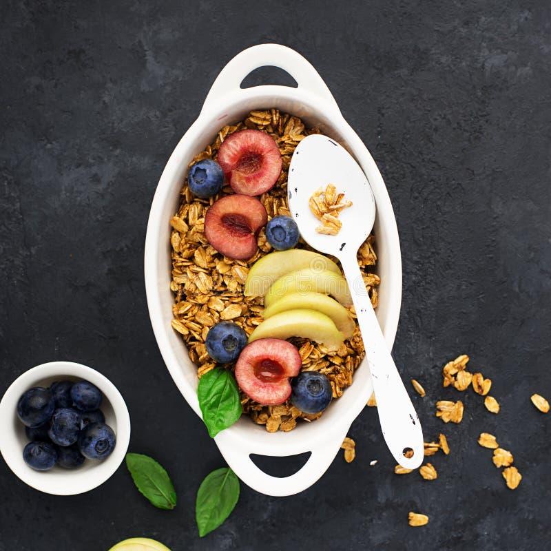 Υγιές ολόκληρο το πρόγευμα σιταριού έψησε το granola από oatmeal τις νιφάδες στην καραμέλα με τα φρέσκους μούρα και τους καρπούς  στοκ εικόνες