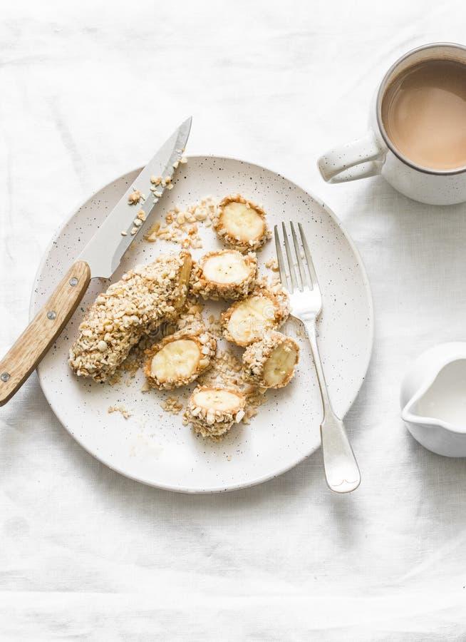 Υγιές πρωτεϊνικό πρόχειρο φαγητό, πρόγευμα - φυστικοβούτυρο, σπόροι, δαγκώματα καρυδιών μπανανών σε ένα ελαφρύ υπόβαθρο στοκ εικόνες