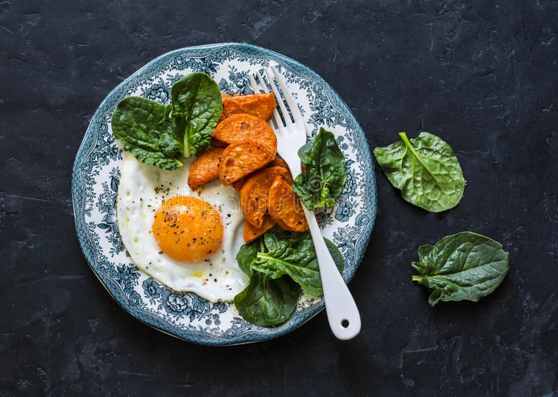 Υγιές πρόγευμα ή πρόχειρο φαγητό - τηγανισμένο αυγό, ψημένα γλυκιά πατάτα και σπανάκι στο σκοτεινό υπόβαθρο, τοπ άποψη στοκ εικόνα με δικαίωμα ελεύθερης χρήσης