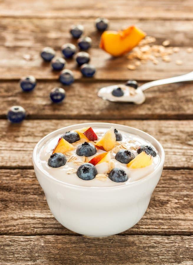 Υγιές πρόγευμα - γιαούρτι με τις νιφάδες και τα βακκίνια βρωμών στοκ φωτογραφίες με δικαίωμα ελεύθερης χρήσης