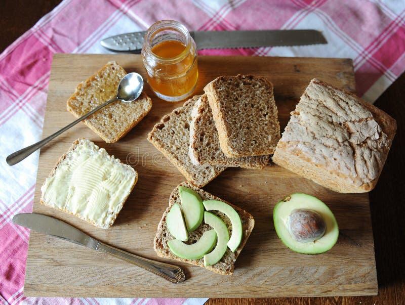 Υγιές πρόγευμα με το φρέσκα ψωμί, το αβοκάντο, τη μαρμελάδα μελιού και το βούτυρο σε έναν ξύλινο πίνακα στο τραπεζομάντιλο καρό στοκ εικόνες