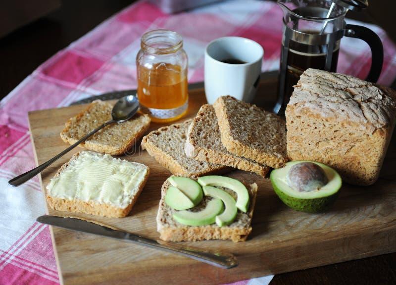 Υγιές πρόγευμα με το φρέσκους ψωμί, τον καφέ, το αβοκάντο, τη μαρμελάδα μελιού και το βούτυρο σε έναν ξύλινο πίνακα στο τραπεζομά στοκ φωτογραφίες με δικαίωμα ελεύθερης χρήσης