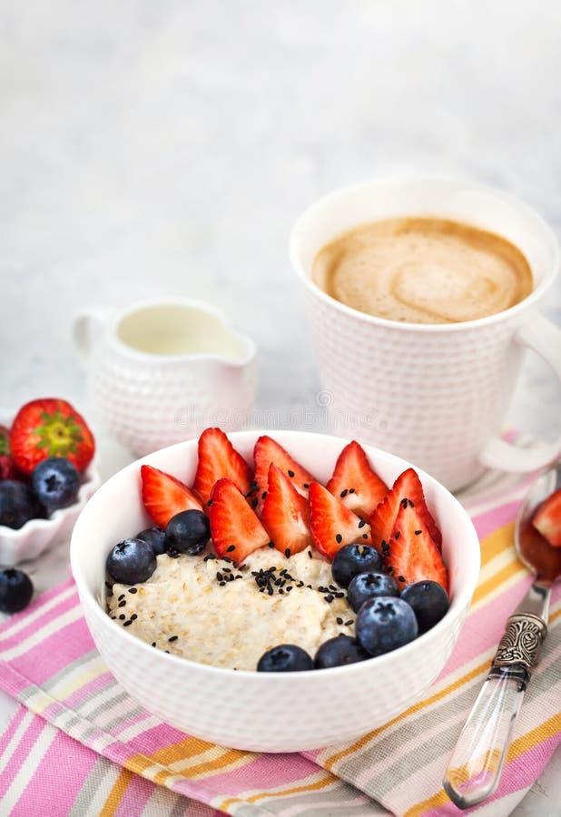 Υγιές πρόγευμα με oatmeal το κουάκερ, τα φρέσκους μούρα και τον καφέ στοκ φωτογραφίες