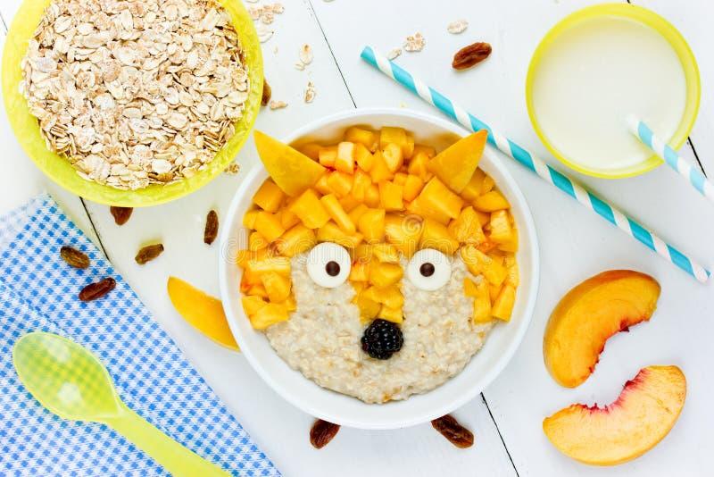 Υγιές πρόγευμα μωρών - γλυκό oatmeal γάλακτος κουάκερ με το ροδάκινο στοκ εικόνες