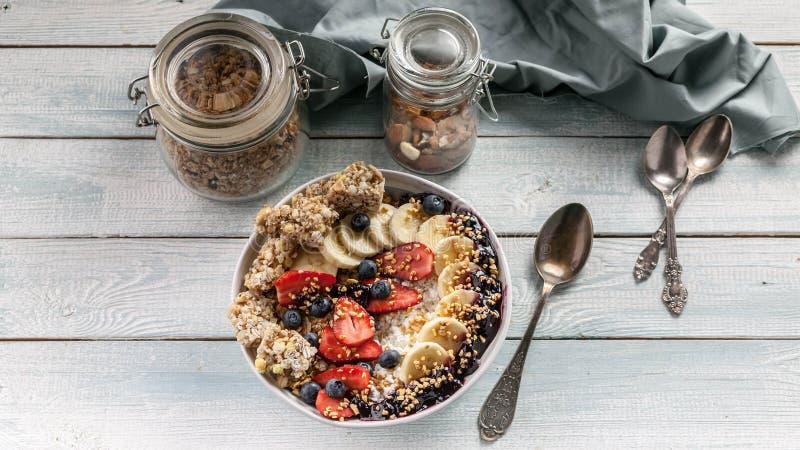 Έμβλημα τροφίμων Υγιές πρόγευμα σε ένα κύπελλο: Τυρί εξοχικών σπιτιών, granola, μπανάνες, φράουλες, βακκίνια και ξεφγμένο ρύζι Ξύ στοκ φωτογραφία με δικαίωμα ελεύθερης χρήσης