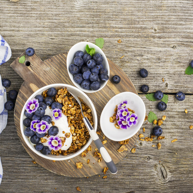 Υγιές πρόγευμα: σπιτικό ψημένο granola με τα βακκίνια, τα φρούτα ακτινίδιων και τα εδώδιμα λουλούδια στο ξύλινο υπόβαθρο από στοκ φωτογραφία