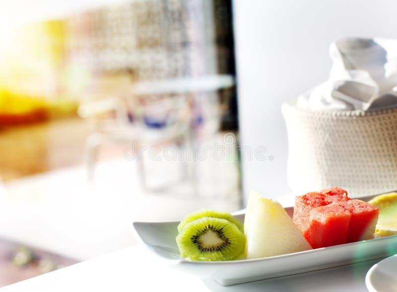 Υγιές πρόγευμα στο παράθυρο Εύγευστα φρούτα με τον ήλιο ανατολής στοκ εικόνα