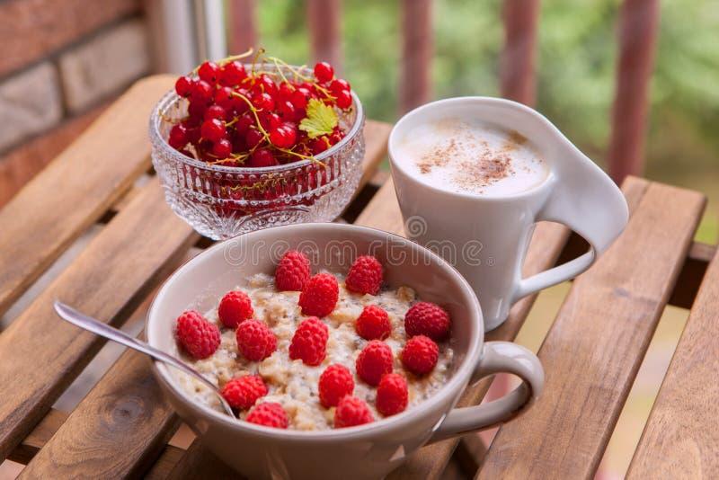 Υγιές πρόγευμα: oatmeal με τα φρέσκα μούρα σε ένα κύπελλο με ένα φλιτζάνι του καφέ στοκ φωτογραφίες με δικαίωμα ελεύθερης χρήσης
