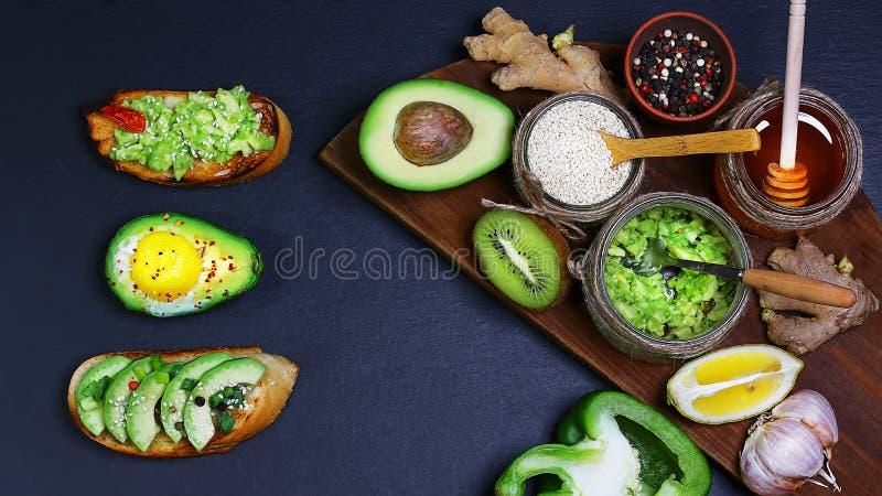 Υγιές πρόχειρο φαγητό μεσημεριανού γεύματος, τρία εύγευστα σάντουιτς αβοκάντο, φρέσκα τεμαχισμένα αβοκάντο, πιπέρι, λεμόνι, σουσά στοκ εικόνα με δικαίωμα ελεύθερης χρήσης