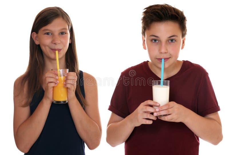 Υγιές πόσιμο γάλα παιδιών κατανάλωσης και χυμός από πορτοκάλι στοκ εικόνες με δικαίωμα ελεύθερης χρήσης