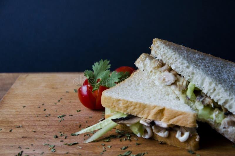 Υγιές σάντουιτς που κόβεται στο μισό στα νόστιμα συστατικά επίδειξης του κοτόπουλου, των μανιταριών και του αγγουριού που παρουσι στοκ εικόνες