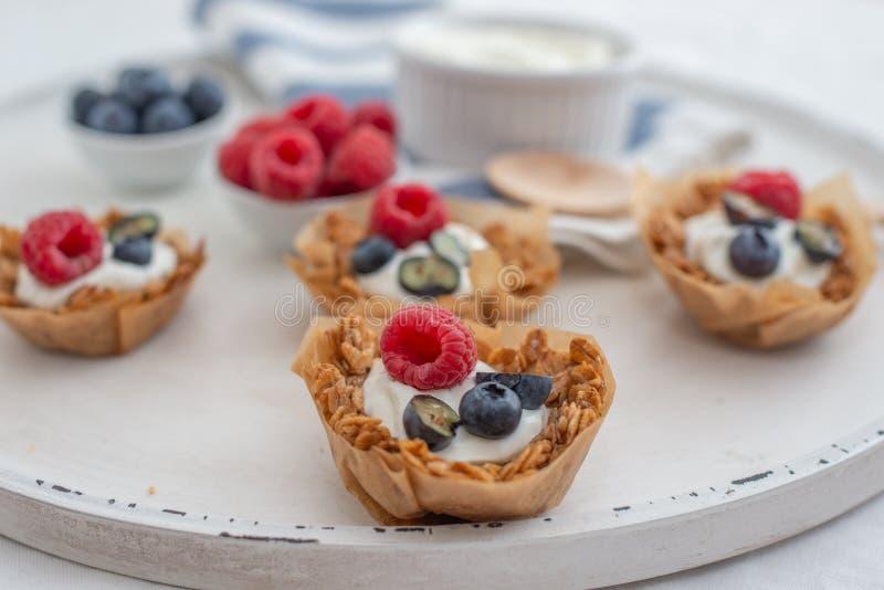 Υγιές σπίτι που γίνεται τα φλυτζάνια granola με το ελληνικά γιαούρτι και τα μούρα στοκ φωτογραφία