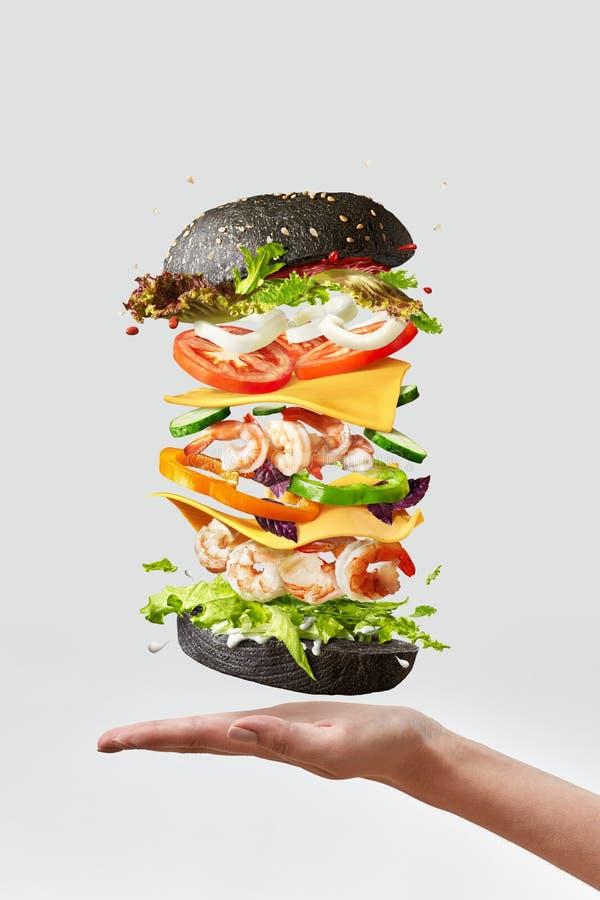 Υγιές σπιτικό burger με τις φρέσκα γαρίδες και τα λαχανικά επάνω από το χέρι σε ένα ελαφρύ υπόβαθρο στοκ εικόνα