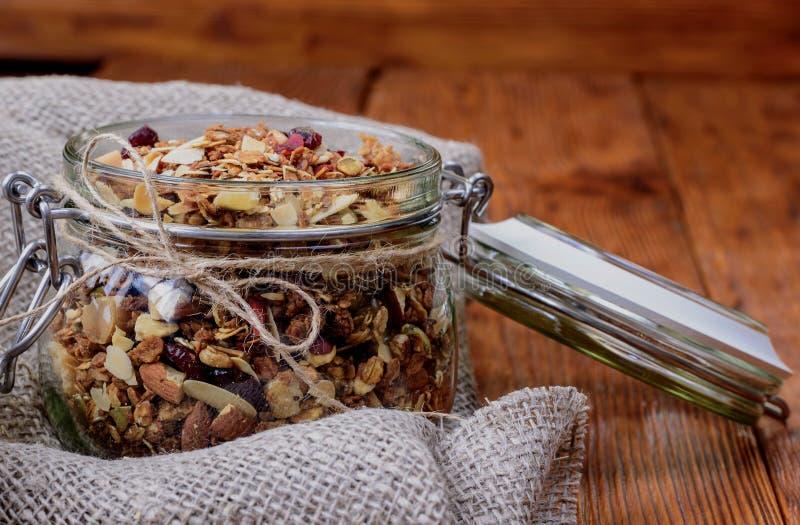 Υγιές σπιτικό granola προγευμάτων στο βάζο γυαλιού στο ξύλινο backgr στοκ εικόνες