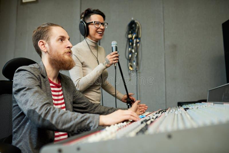 Υγιές τραγούδι καταγραφής σχεδιαστών και τραγουδιστών στο στούντιο παραγωγής στοκ εικόνα