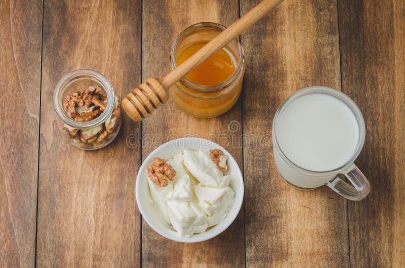 Υγιές υπόβαθρο προγευμάτων Μέλι, γάλα, τυρί εξοχικών σπιτιών και ξύλο καρυδιάς σε ένα ξύλινο υπόβαθρο r στοκ φωτογραφία με δικαίωμα ελεύθερης χρήσης
