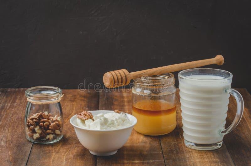 Υγιές υπόβαθρο προγευμάτων Μέλι, γάλα, τυρί εξοχικών σπιτιών και ξύλο καρυδιάς σε ένα ξύλινο υπόβαθρο στοκ φωτογραφία με δικαίωμα ελεύθερης χρήσης