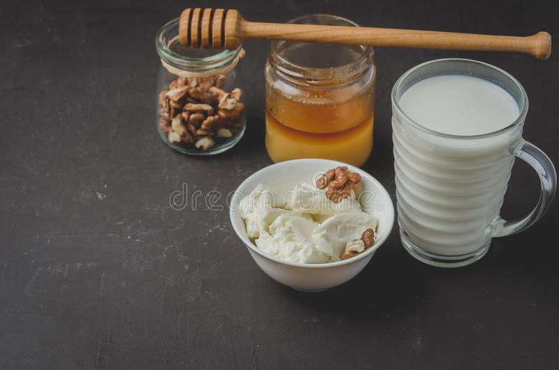 Υγιές υπόβαθρο προγευμάτων Μέλι, γάλα, τυρί εξοχικών σπιτιών και ξύλο καρυδιάς σε ένα υπόβαθρο πετρών r στοκ εικόνες