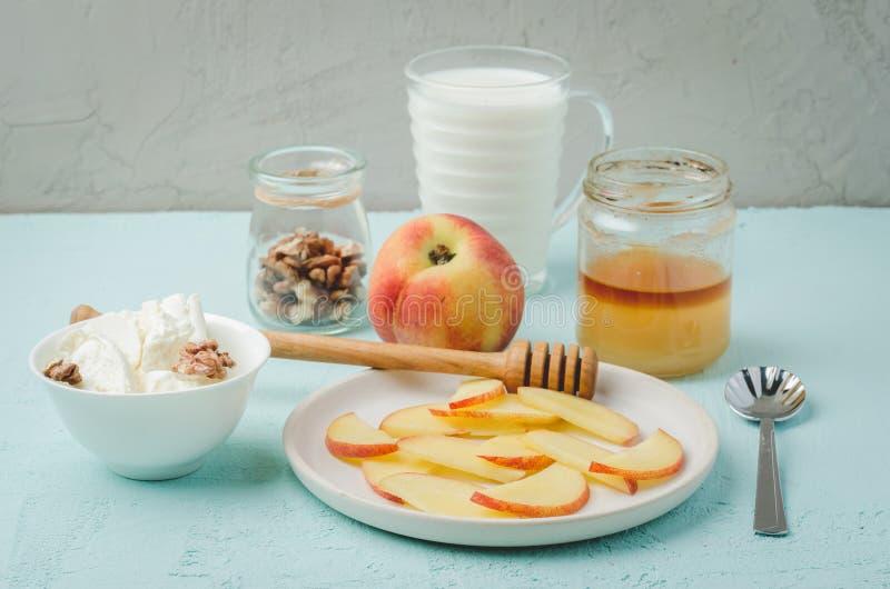 Υγιές υπόβαθρο προγευμάτων Ροδάκινο, μέλι, γάλα, τυρί εξοχικών σπιτιών και ξύλο καρυδιάς σε ένα μπλε υπόβαθρο r στοκ εικόνα