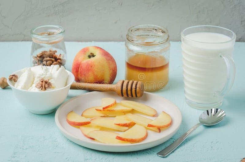 Υγιές υπόβαθρο προγευμάτων Ροδάκινο, μέλι, γάλα, τυρί εξοχικών σπιτιών και ξύλο καρυδιάς σε ένα μπλε υπόβαθρο στοκ εικόνα με δικαίωμα ελεύθερης χρήσης