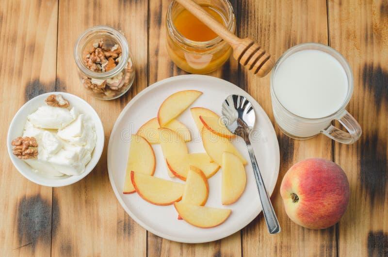 Υγιές υπόβαθρο προγευμάτων Ροδάκινο, μέλι, γάλα, τυρί εξοχικών σπιτιών και ξύλο καρυδιάς σε ένα ξύλινο υπόβαθρο r στοκ φωτογραφία