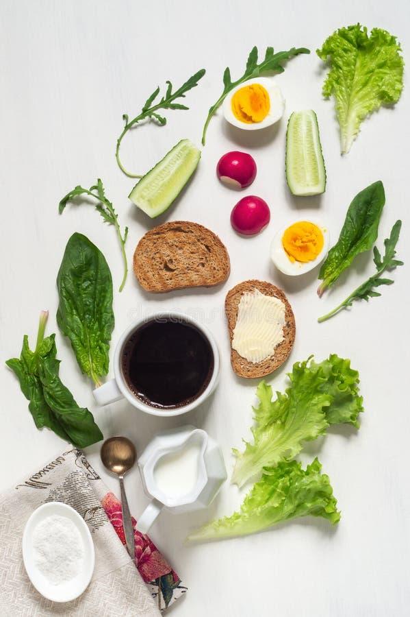 Υγιές φλιτζάνι του καφέ, αυγά, φρυγανιά με το βούτυρο και φύλλα προγευμάτων του σπανακιού στοκ φωτογραφία με δικαίωμα ελεύθερης χρήσης