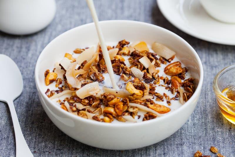Υγιές φρέσκο granola προγευμάτων, muesli με την έκχυση του γάλακτος σε ένα άσπρο κύπελλο στο γκρίζο υφαντικό υπόβαθρο στοκ φωτογραφία