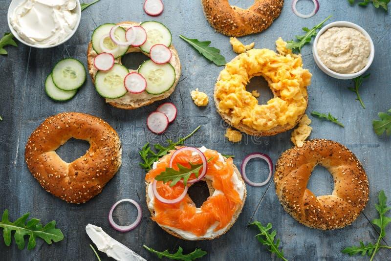 Υγιές Bagels σάντουιτς προγευμάτων με το σολομό, τα ανακατωμένα αυγά, τα λαχανικά και το τυρί κρέμας στοκ φωτογραφία με δικαίωμα ελεύθερης χρήσης