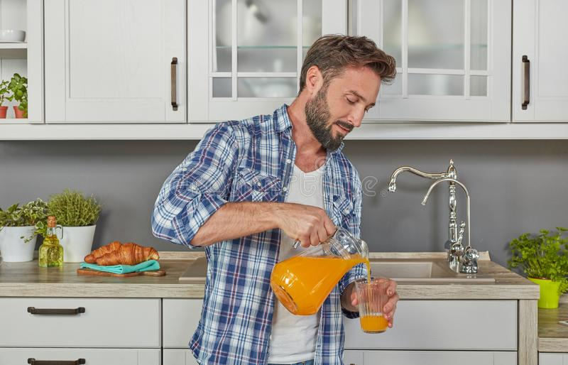 Υγιής άνδρας που πίνει το χυμό από πορτοκάλι στοκ εικόνες