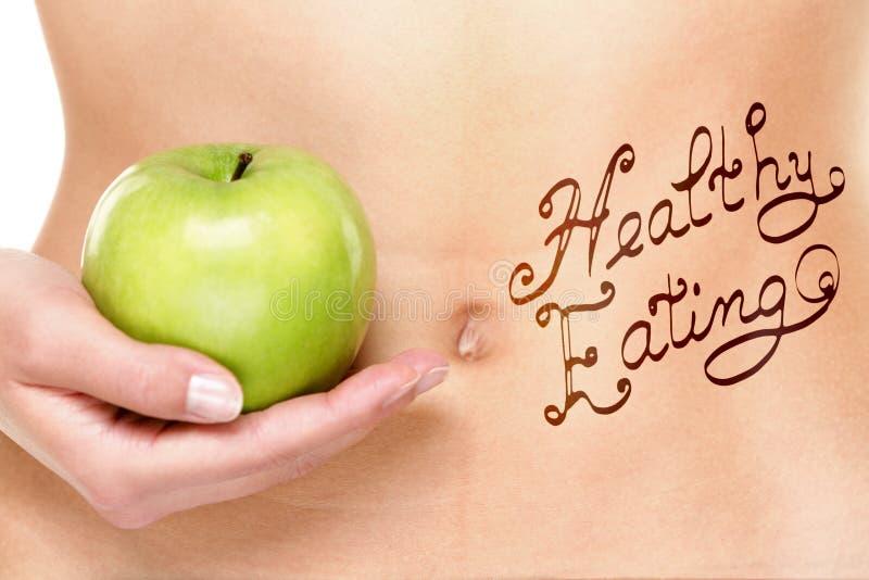 Υγιής έννοια κατανάλωσης - στομάχι και μήλο γυναικών στοκ φωτογραφία