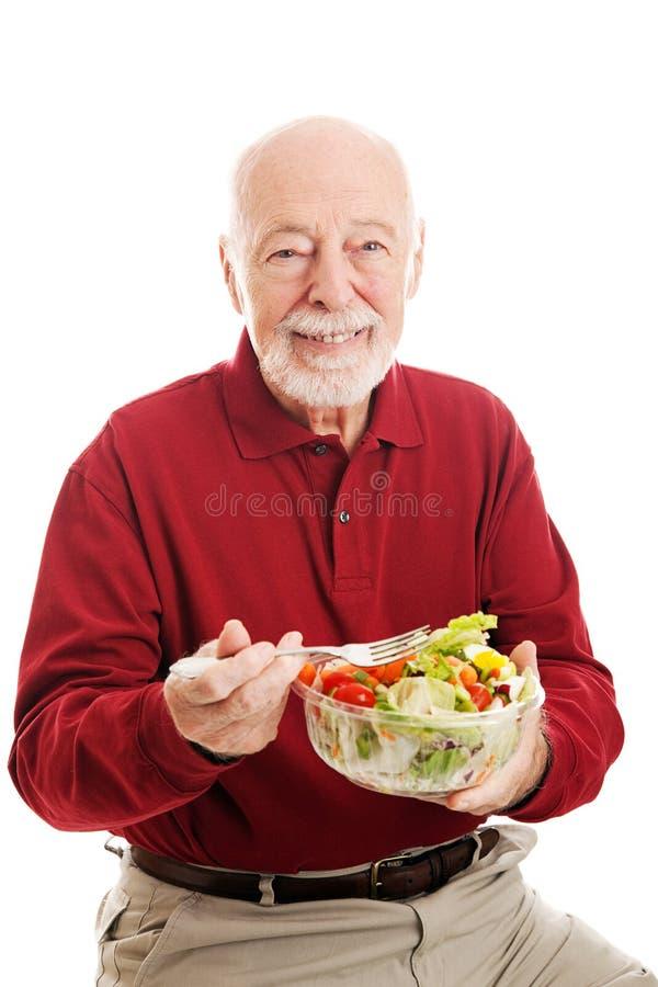 Υγιής ανώτερος άνδρας που τρώει τη σαλάτα στοκ εικόνες