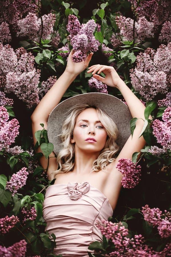 Υγιής γυναίκα με τα ιώδη λουλούδια στοκ εικόνες