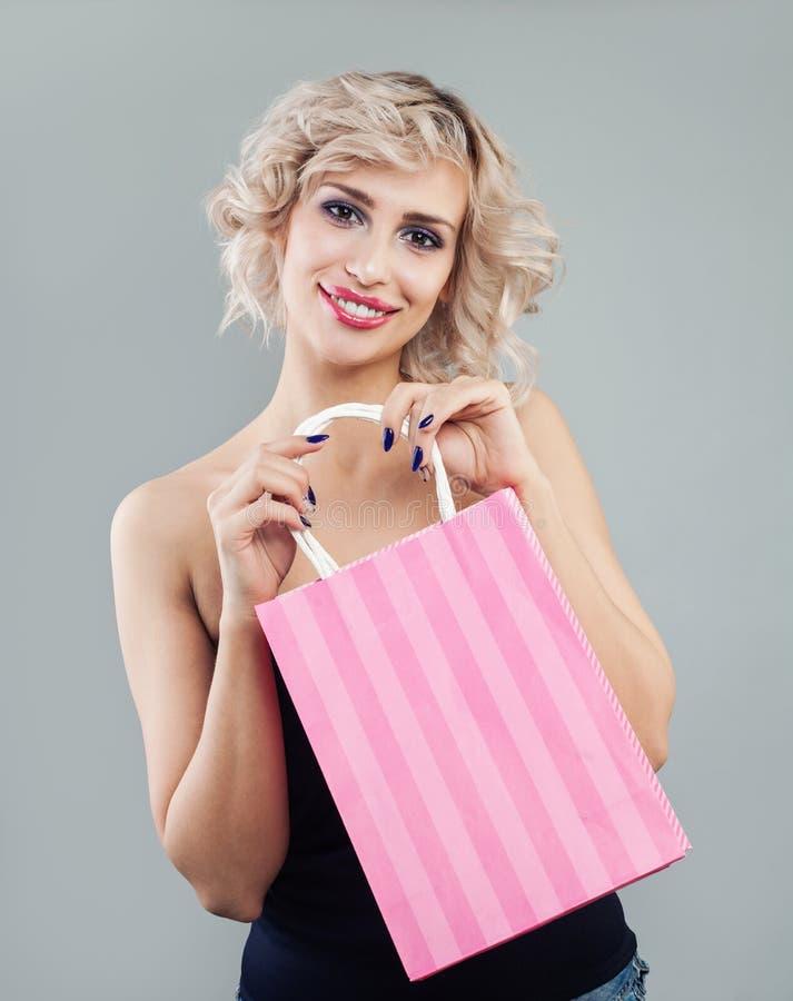 Υγιής γυναίκα με τις τσάντες αγορών Τέλειο πρότυπο με το makeup και τη σύντομη σγουρή τρίχα στοκ εικόνες