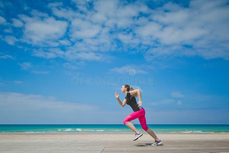 Υγιής γυναίκα που τρέχει στην παραλία, κορίτσι που κάνει το αθλητικό υπαίθριο, ευτυχές θηλυκό που ασκούν, την ελευθερία, διακοπές στοκ εικόνα