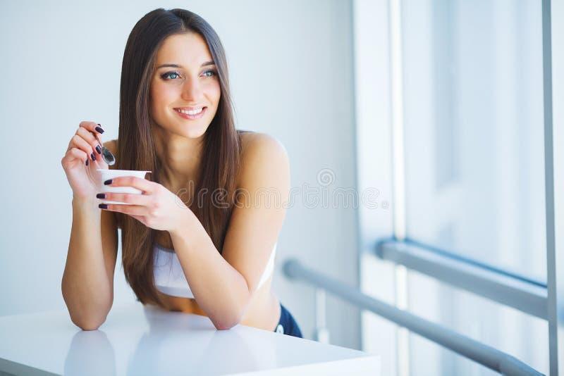 Υγιής γυναίκα προγευμάτων με το ποτήρι του γιαουρτιού, των μούρων και των βρωμών στοκ εικόνες
