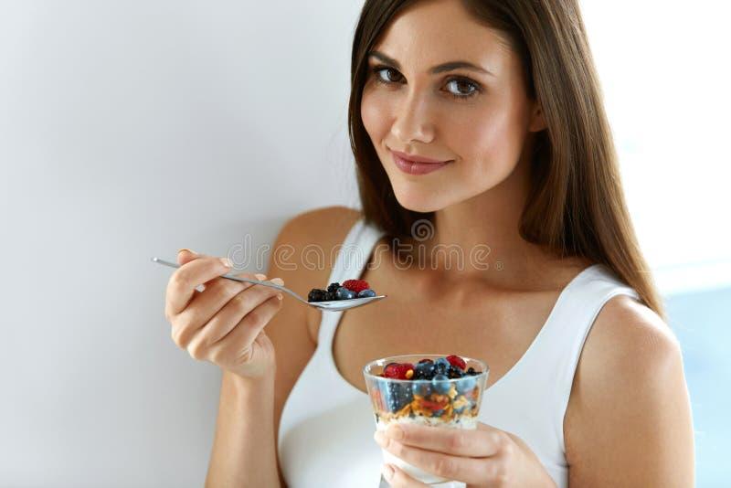 Υγιής γυναίκα προγευμάτων με το ποτήρι του γιαουρτιού, των μούρων και των βρωμών στοκ φωτογραφίες με δικαίωμα ελεύθερης χρήσης