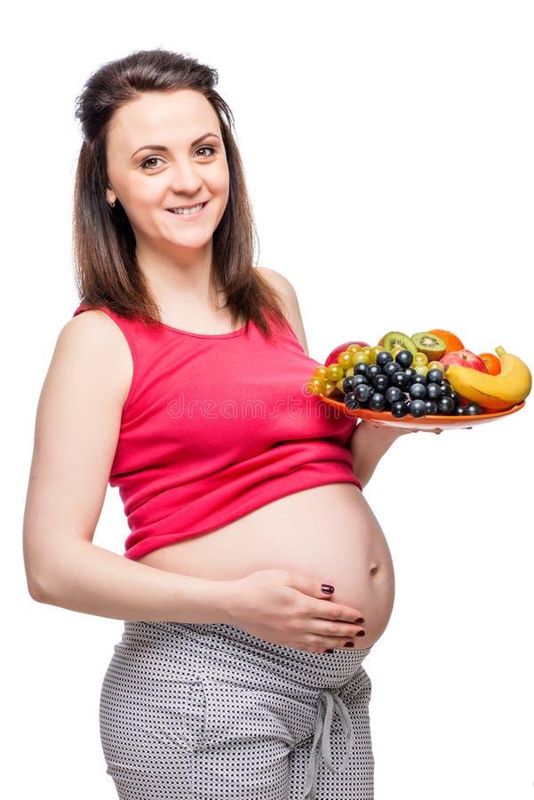 υγιής ευτυχής έγκυος γυναίκα με ένα πιάτο των φρούτων στοκ εικόνα με δικαίωμα ελεύθερης χρήσης
