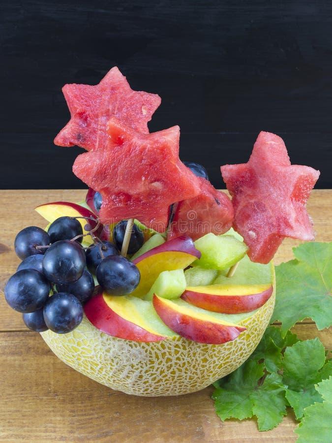 Υγιής ελκυστική σαλάτα φρούτων που εξυπηρετείται σε ένα φρέσκο πεπόνι ενάντια στο β στοκ φωτογραφίες