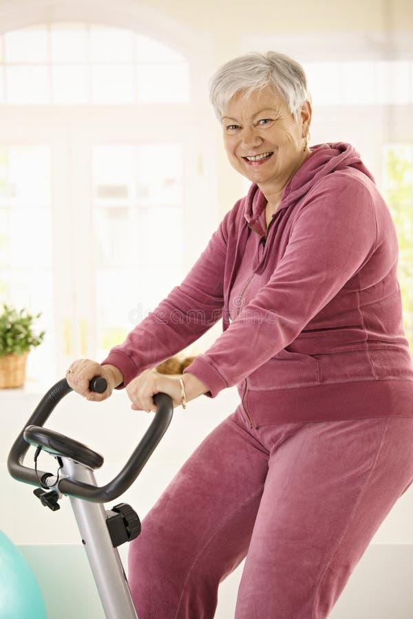 Υγιής ηλικιωμένη γυναίκα στο ποδήλατο άσκησης στοκ εικόνες
