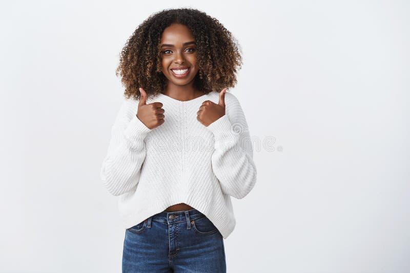 Υγιής καλός με μετρά μέσα Γοητευτικός τη φιλική γυναίκα αφροαμερικάνων σγουρός-μαλλιαρή παρουσιάστε αντίχειρας-επάνω όπως τη χειρ στοκ εικόνα