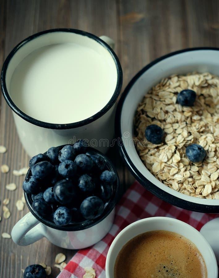 Υγιής κατανάλωση, τρόφιμα και έννοια διατροφής - νόστιμο oatmeal με τα μούρα και μια κούπα του γάλακτος και ενός φλιτζανιού του κ στοκ εικόνα με δικαίωμα ελεύθερης χρήσης