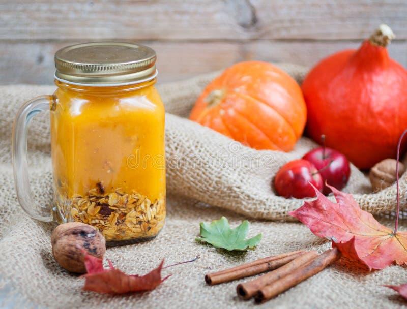 Υγιής καταφερτζής προγευμάτων Α φιαγμένος από κολοκύθα και μήλα με το granola και καρύδια σε ένα βάζο κτιστών στοκ φωτογραφία