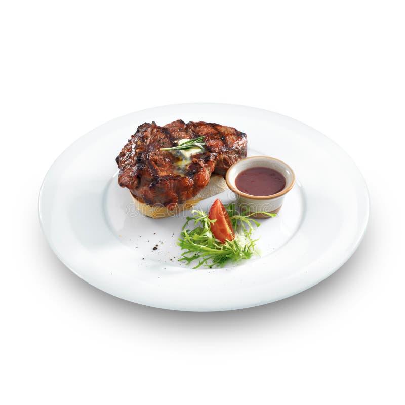 Υγιής καλοψημένη μπριζόλα κρέατος με το βούτυρο και τα χορτάρια στοκ εικόνα