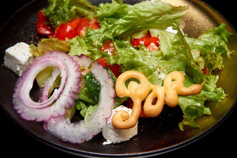 Υγιής μικτή σαλάτα με τα πράσινα, το αγγούρι, το κρεμμύδι, τις ντομάτες και το τυρί φέτας στοκ εικόνα