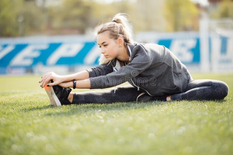 Υγιής νέα γυναίκα που ασκεί στο πάρκο Κατάλληλη νέα γυναίκα που κάνει την κατάρτιση workout το πρωί στη χλόη στοκ εικόνα