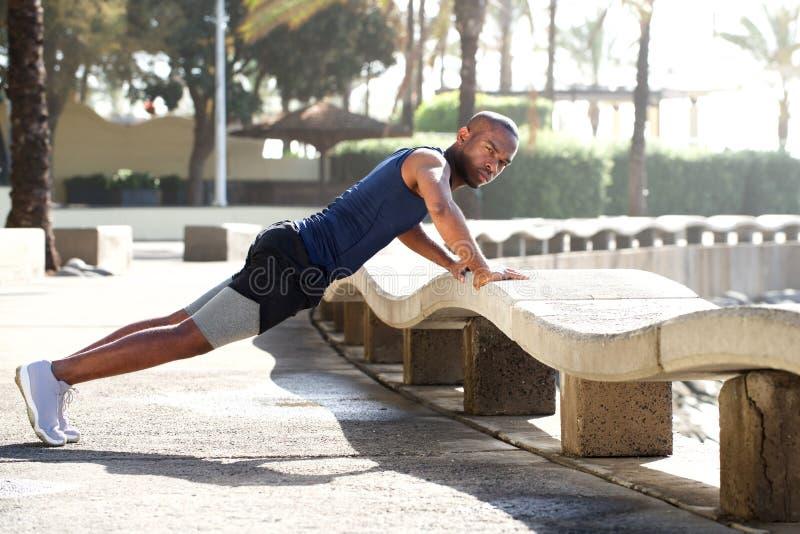 Υγιής νεαρός άνδρας που κάνει pushups υπαίθρια στοκ εικόνες