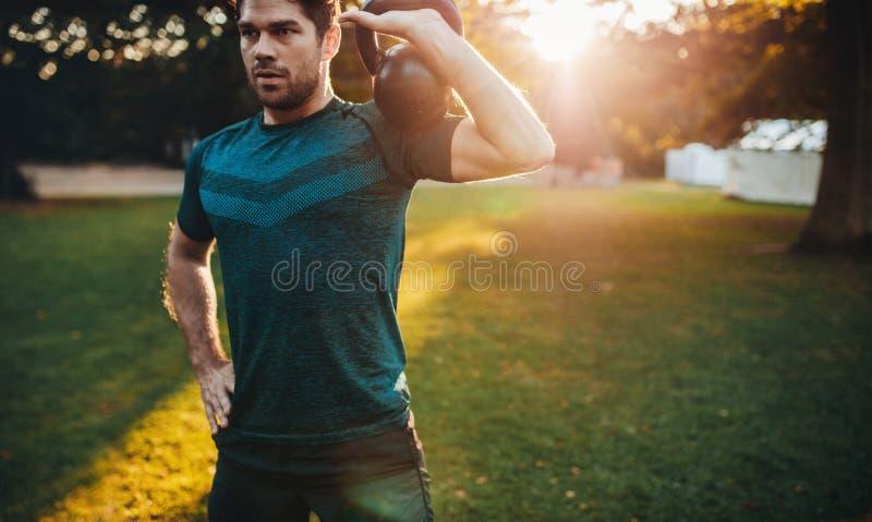 Υγιής νεαρός άνδρας που επιλύει με το kettlebell στοκ φωτογραφία